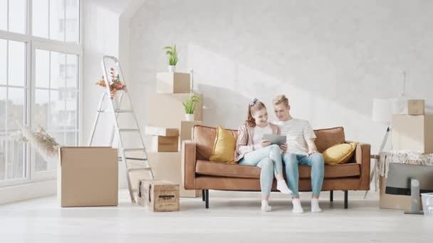Junges Paar sitzt mit Tablet auf Couch in neuem Zuhause Paar im Gespräch über neue Heimat. Glückliches Paar entspannt zu Hause vor dem Tablet.