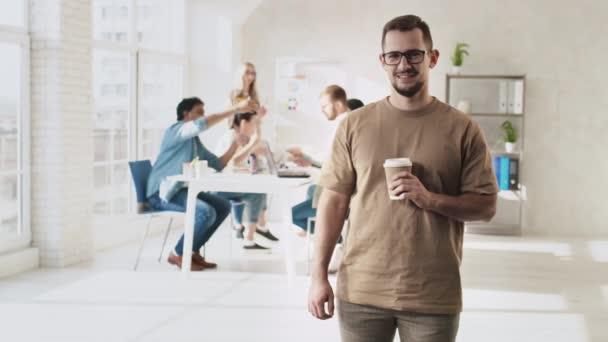 Férfi áll a kreatív iroda kezében kávé menni Cup. Egy férfi kávéscsészével. A kreatív csapat az irodában dolgozik. Vörösre lőtték.