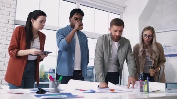 Kreatives Team am Tisch. Kreative Büroarbeit. Team diskutiert Ideen. Architektur Tischarbeit. Schuss auf ROT