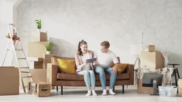 Fiatal pár ül a kanapén az új otthon használja Tablet. Egy pár az új otthonról tárgyal. Egy boldog pár lazít a Home Watch Tablet-ben. Vörösre lőtték.