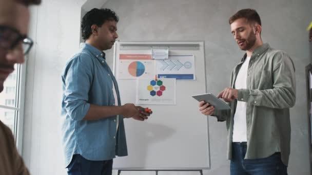 Der Mann, der im Kreativbüro am PC arbeitet. Team diskutiert Präsentation im Amt. Kreative Büroarbeit. Schuss auf ROT. Blick nach draußen