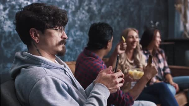 Friends Chatting Drinking Beer at Home. Indian Man is Chatting on Phone. Not with Friends. Lonely man Chatting on Phone While Friends are Having Fun. Phone addicted