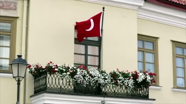 Turecká vlajka vlající ve větru na balkón s květy