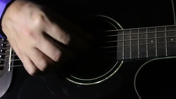 Mans hand playing the guitar
