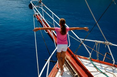 Young girl on the boat with hands in an imaginary flight
