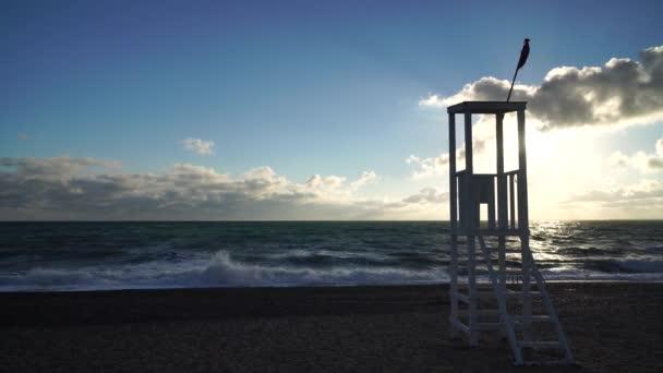fa mentési megfigyelő állomás és homokos strand azúrkék viharos tenger, felhős ég háttér. Üres strand napszemüveggel. Evpatoriya, Krím. A nyugalom, a csend és a természettel való egység fogalma.