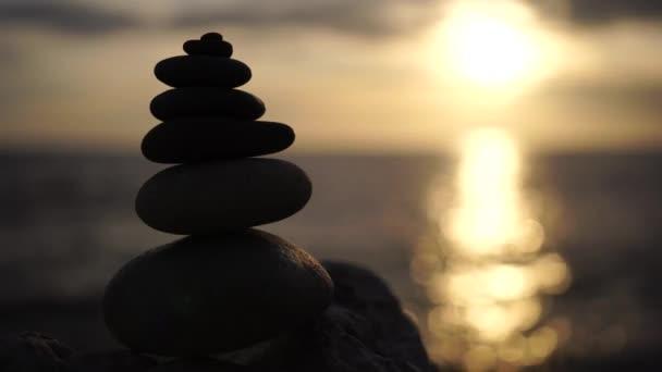 Kiegyensúlyozott kavicsos piramis meleg naplementével a parton. Absztrakt Sea bokeh a háttérben. Szelektív fókusz. Zen kövek a tengerparton, meditáció, spa, harmónia, nyugalom, egyensúly koncepció