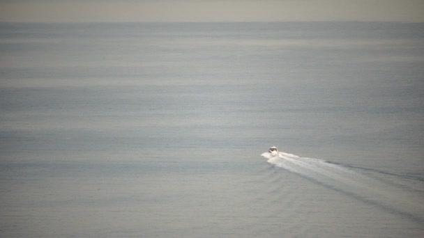 Motorový člun plující rychle v klidném moři na pozadí mořské krajiny s skalnatým pobřežím. Koncept ideálního místa pro letní cestování a odpočinek.