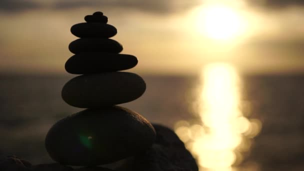Slow motion. Balanced pebble pyramid with warm sunset on the beach. Abstract Sea bokeh on the background. Selective focus. Zen stones on the sea beach, meditation spa harmony calmness, balance concept