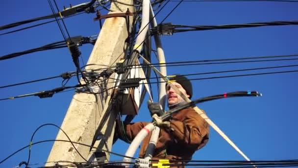Detailní záběr na Elektrikáře instalujícího dráty, kabely do elektrického štítu, pojistkovou skříň, průmyslový elektrický panel se spoustou barevných kabelů a drátů. Koncept energetického průmyslu.