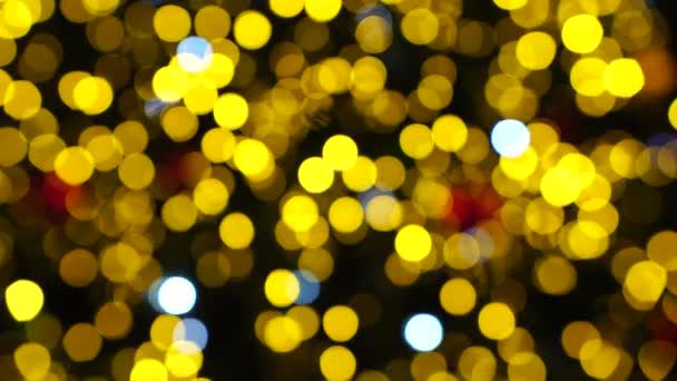Rozmazané vánoční pozadí. Zářivě červená a zlatá světla s měkkým ostřením. Lens Bokeh. Světlomety. Vánoční strom s blikajícími věnci. Nový rok a vánoční ozdoby. Tmavé pozadí.