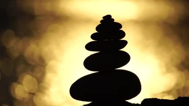 Vyvážená oblázková pyramida s teplým západem slunce na pláži. Abstraktní mořský bokeh na pozadí. Selektivní soustředění. Zenové kameny na mořské pláži, meditace, lázně, harmonie, klid, rovnováha koncept