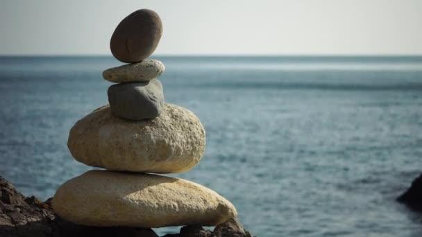 Balanced pebble pyramid on the beach on a sunset time. Sea waves on the background. Selective focus. Zen stones on the sea beach, meditation, spa, harmony, calmness, balance concept
