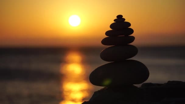 Balanced pebble pyramid with warm sunset on the beach. Abstract Sea bokeh on the background. Selective focus. Zen stones on the sea beach, meditation, spa, harmony, calmness, balance concept