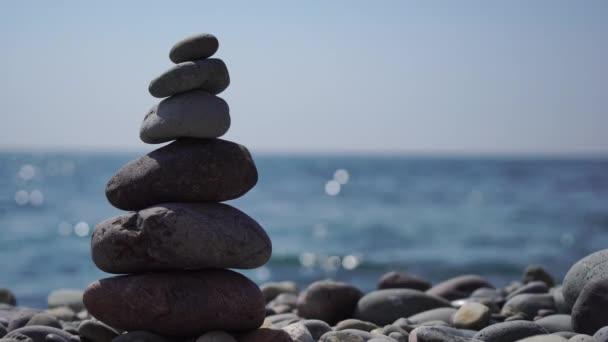 Pyramidové kameny na pobřeží za slunečného dne na modrém mořském pozadí. Šťastné svátky. Oblázková pláž, klidné moře, místo pro cestování. Koncept šťastné dovolené na moři, meditace, lázně, klid.