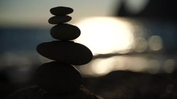 Balanced pebble pyramid on the beach on a sunny day. Abstract Sea bokeh from sunset on background. Selective focus. Zen stones on the sea beach, meditation, spa, harmony, calmness, balance concept