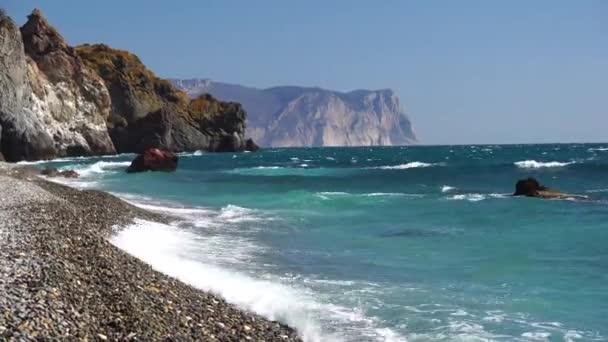 výhled na západ slunce a pláž, sopečná skála je osvětlena teplým západem slunce, pískem a oblázky, sopečným čedičem jako na Islandu. Rozumím. Koncept klidu, ticha a jednoty s přírodou.