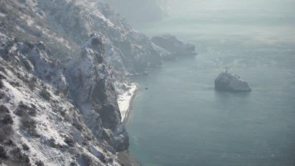 Snow pokrýval skalnaté útesy nad mořem. Zimní krajina nad mořským zálivem. Jalovec pod sněhem. Koncept zimních prázdnin, cestování a rekreace. Mys Fiolent v Balaklavě, Sevastopol, Krym