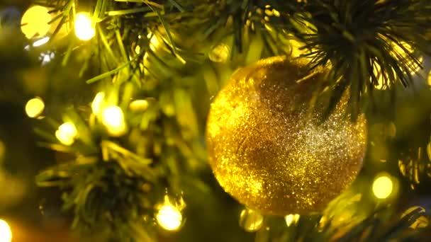 Vánoční strom s blikajícími věnci. Rozmazané vánoční pozadí. Zářivě červená a zlatá světla s měkkým ostřením. Lens Bokeh. Světlomety. Nový rok a vánoční ozdoby. Tmavé pozadí.