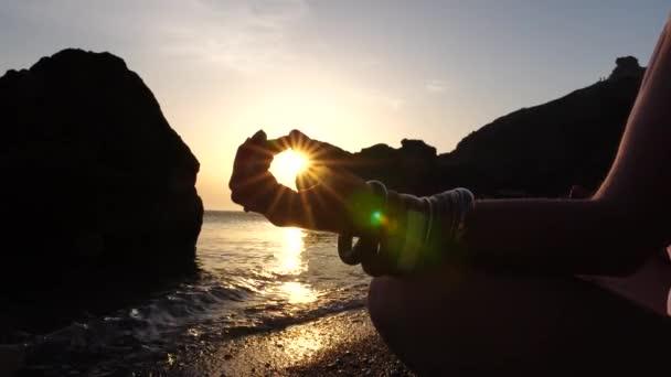Mladá žena s dlouhými vlasy cvičit protahování venku na jóga rohožce u moře za teplého západu slunce. Ženský cvičej pilates jógy. Zdravý životní styl, harmonie a koncepce meditace