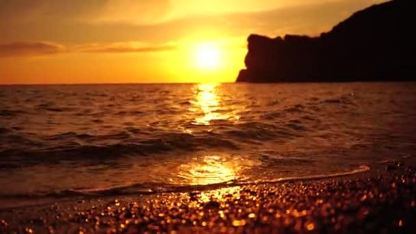 Rudě žhnoucí západ slunce se siluetou útesu nad mořem. Abstraktní příroda léto nebo jaro oceánské moře pozadí. Malé vlny na zlaté teplé vodní hladině s bokeh světla ze slunce.