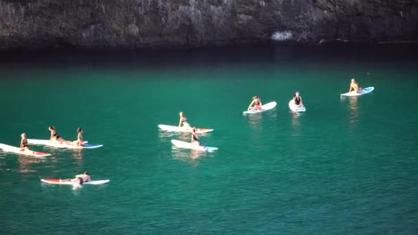 Group of young womens in swimsuit doing yoga on sup board in calm sea, early morning. Balanced pose - concept of healthy life and natural balance between body and mental development.