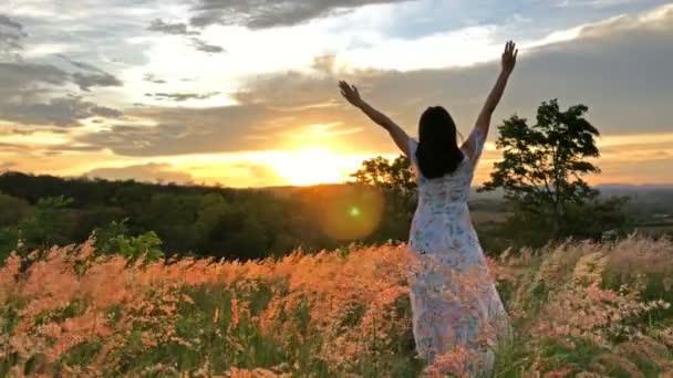 A lány a réten a hegyekkel naplementekor Nyugodtnak és szabadnak érzi magát.