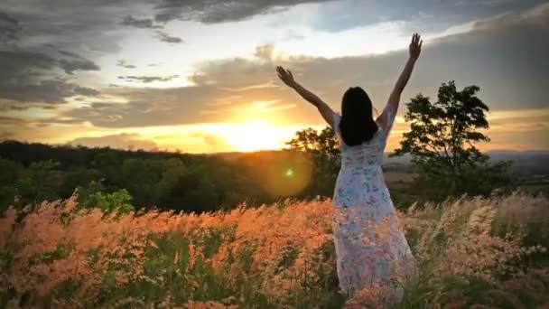 Das Mädchen auf der Wiese mit dem Berg bei Sonnenuntergang Fühlen Sie sich entspannt und frei
