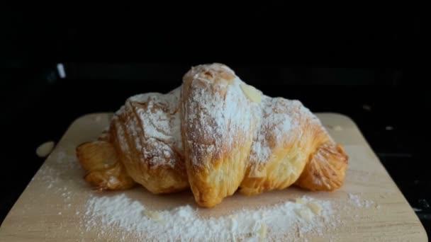 Croissanty s ledovým cukrem na dřevěném talíři posypané mandlemi. Pomalý pohyb