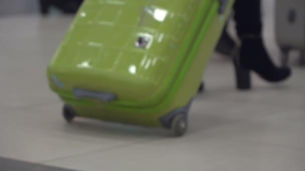 Žena s kufrem v hale letiště
