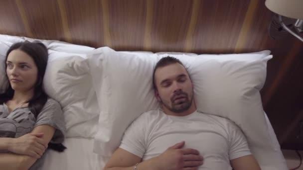Snooring muž a naštvaná žena v posteli