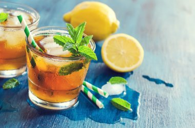 Fresh cold iced tea with mint, ice and lemons, refreshing drink,