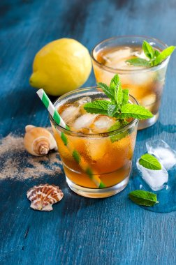 Fresh cold iced tea with mint, ice and lemons, refreshing drink