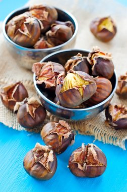 Roasted chestnuts in bowls on sackcloth