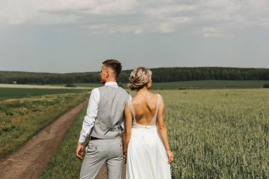 Beautiful happy couple, man and woman are walking in nature together. back view. A young woman in a white dress and a man in trousers and a shirt. Love and Valentines Day concept.