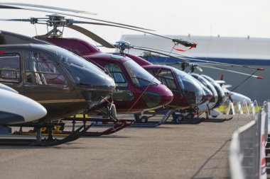 Helicopters lined up on the runway next to each other during the exhibition. No logos.