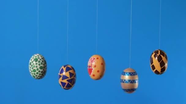 Bunte Ostereier drehen sich um ihre Achse auf blauem Hintergrund mit einem Platz für Text. Osterverkauf, Rabatte oder Aktionen im Werbevideo.