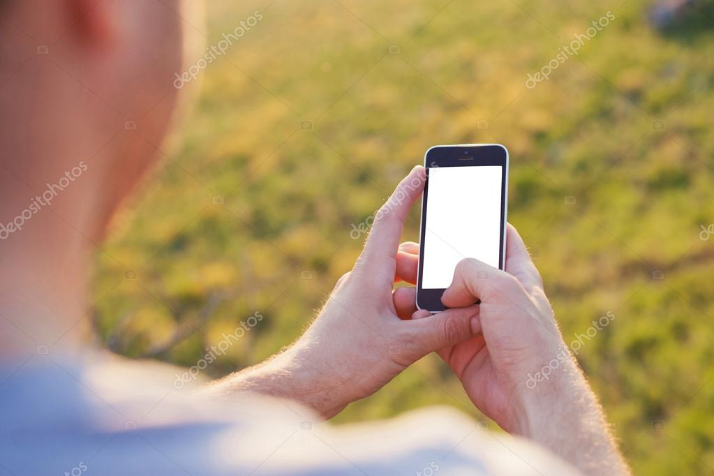 Men's hands hold the smartphone with a white screen
