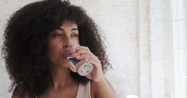Mladá multiiraciální žena pitná voda každodenní ranní zvyk rutina po ranním cvičení