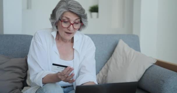 Seniorin mit Brille gibt Geld in Internetseiten und Geschäften aus