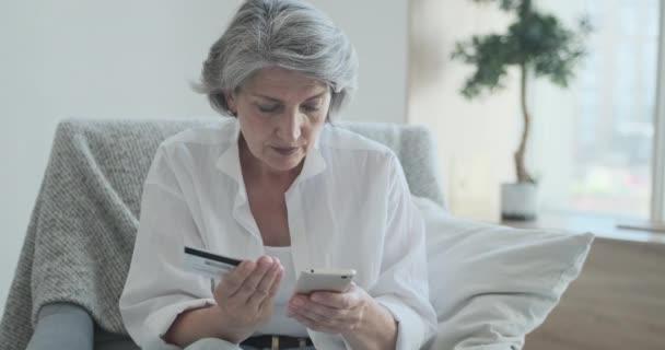 Fokussierte Bankkundin mit Kreditkarte und Handy für sofortige Online-Zahlungen.