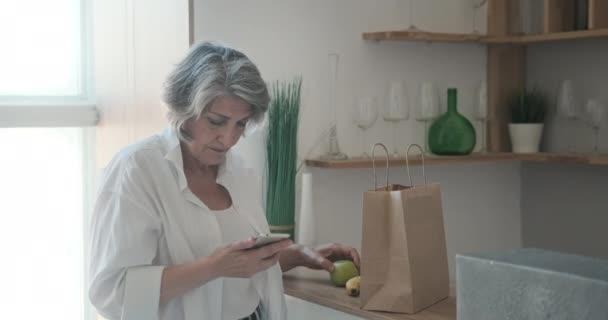 Starší žena dostala zásilku potravin v papírovém sáčku. Online objednávka ovoce a zeleniny