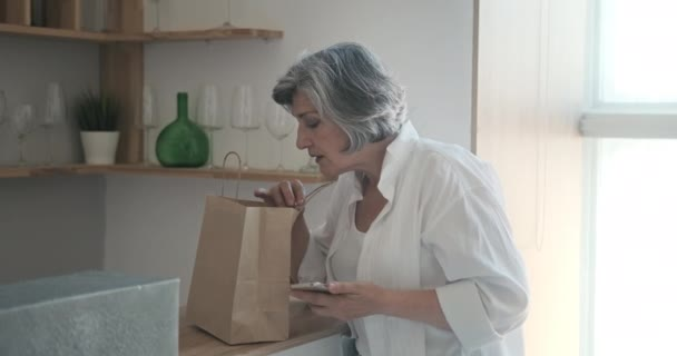 Senior woman received home delivery of groceries in paper bag.