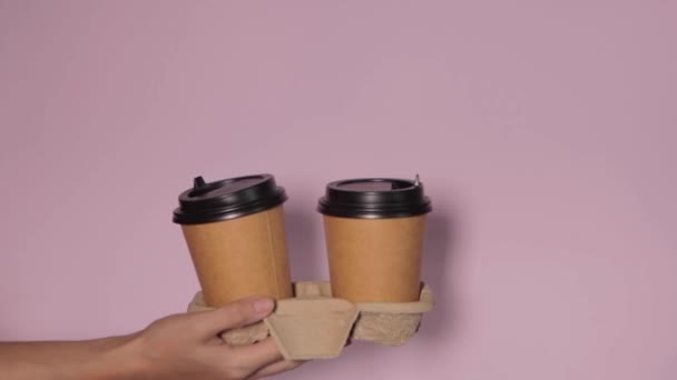 Close-up on a pink background, a womans hand holds a paper cup with coffee in a stand. Coffee or tea to go. People hands passing one another cup of coffee, coffee delivery.