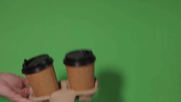 Close-up on a green background, a womans hand holds a paper cup with coffee in a stand. Coffee or tea to go. People hands passing one another cup of coffee, coffee delivery.