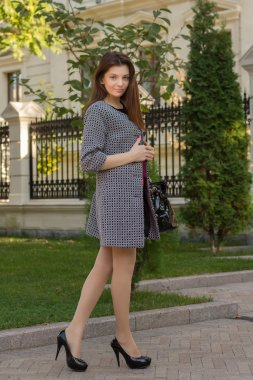 Portrait of young beautiful woman outdoor.Beautiful brunette girl in clothes. Young woman wearing coat walking down the street, warm day.