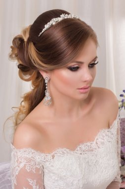 Beauty woman with wedding hairstyle and makeup. Bride fashion. Jewelry and Beauty. Woman in white dress,perfect skin. Girl with stylish haircut.