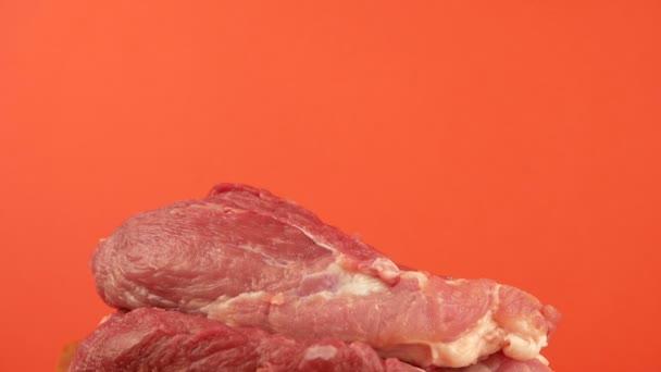 Téma masných výrobků. Velký nůž se zasekne do kusu červeného masa na jasně oranžovém pozadí. Masné výrobky, zpracování masa. Selektivní zaměření, mělká hloubka zaměření