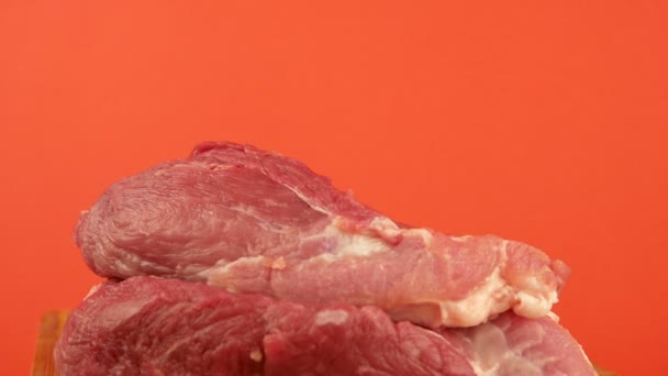 Ostrý velký řeznický nůž se zabodne do syrového červeného masa. Kousky čerstvého vepřového a nůž na jasně oranžovém pozadí. Téma vaření masa a masných výrobků. Klobása. Selektivní zaměření