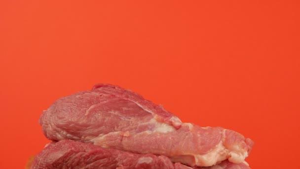 Velký nůž krájí kus syrového čerstvého červeného masa na jasně oranžovém pozadí. Řezník krájí kus vepřového. Kousky masa a nůž. Selektivní zaměření, mělká hloubka pole
